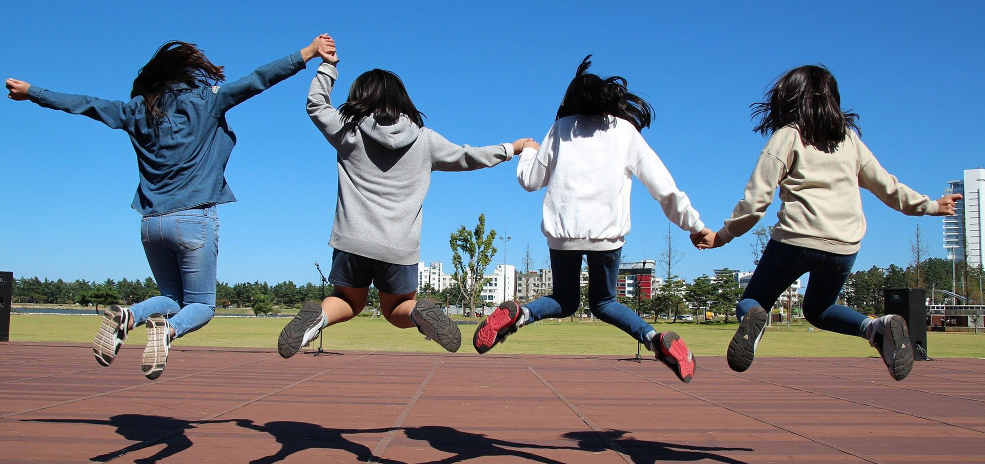 Preteen girls jumping while holding hands