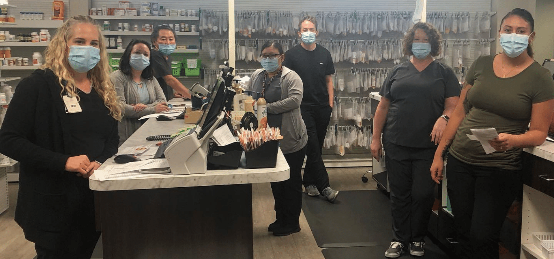 Staff in pharmacy setting with masks.