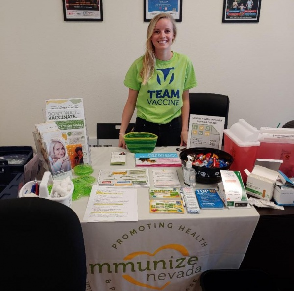Nina A. stands behind an outreach table at a community event.